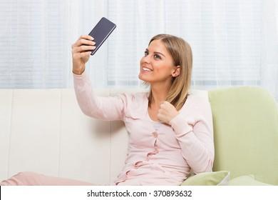 Beautiful woman sitting on sofa and taking selfie.Woman taking selfie