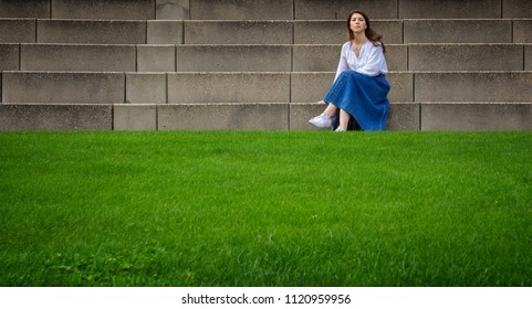 Beautiful woman sitting on stone steps in front of the bright green grass. Fashionable photo.
