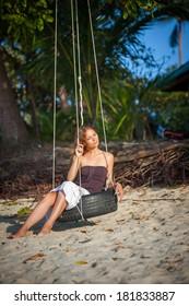 Beautiful woman sitting on the swing on paradise beach on Samui