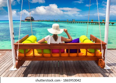 Beautiful woman is sitting on swing at luxury tropical beach in a sunny summer day