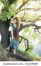 Beautiful woman sitting on tree at nature in sunny day