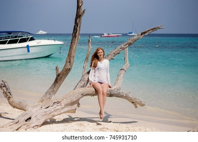 Beautiful woman sitting on a tree trunk at the beach