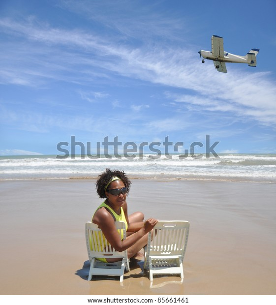 Beautiful Woman sitting on Tropical beach Look at Camera Small Airborne Airplane Flying Over Beautiful Blue Cloud Sky