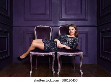Beautiful woman is sitting on two chairs, a concept