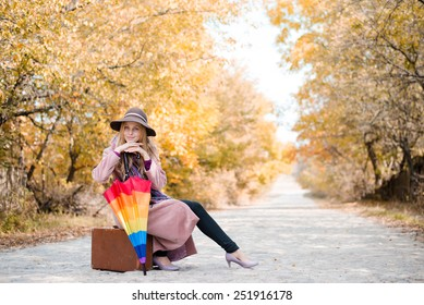 Beautiful woman sitting on a vintage suitcase with umbrella on a desert road