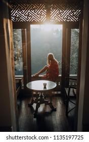 Beautiful woman sitting on window ledge at sunrise in Bali forest
