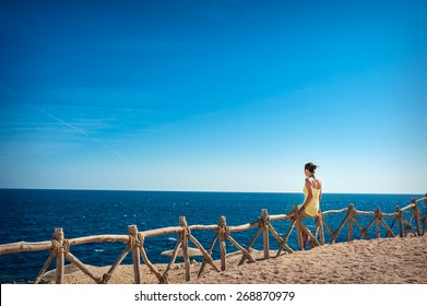 beautiful woman sitting on a wooden fence and looking at the sea.
