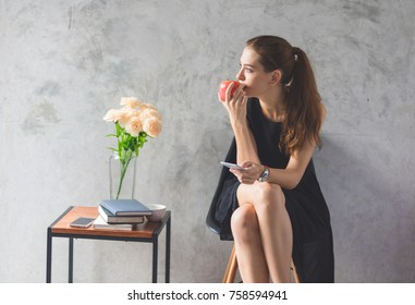 Beautiful woman sitting in the phone and holding a red apple in the room.