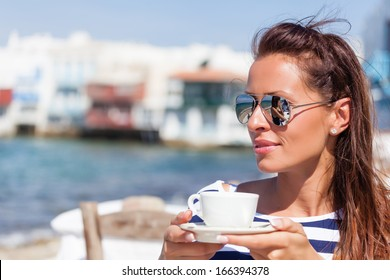Beautiful woman sitting at a seaside cafe and drinks a coffee