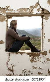 A Beautiful woman sitting and staring out of a window frame of old building
