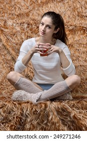 Beautiful woman sitting in Studio with fur background.