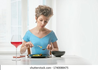 Beautiful woman sitting at the table by the windowand is eating vegetable salad