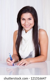 Beautiful woman sitting at a table smiling happily and writing notes on a sheet of paper