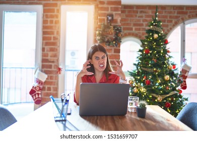 Beautiful woman sitting at the table working with laptop at home around christmas tree Shouting frustrated with rage, hands trying to strangle, yelling mad