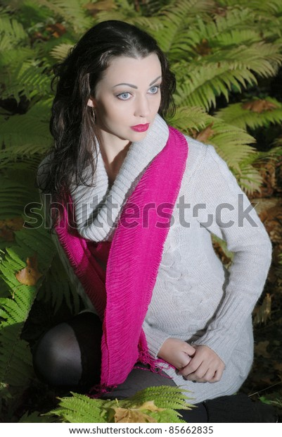 Beautiful Woman sitting in the undergrowth of fern at the night time