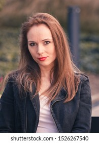 Beautiful woman sitting in urban park relaxing place wearing black jeans jacket. Female fashion model during spring weather, having long brown hair wind tousled.