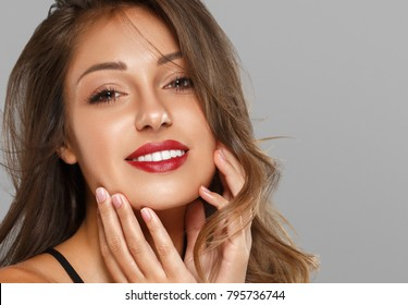 Beautiful Woman Skin Tanned Red Lips Healthy Beauty Skin Smile. Spa Beautiful Model Girl Cute Face over gray background.