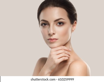 Beautiful woman skincare portrait with hand over beige background