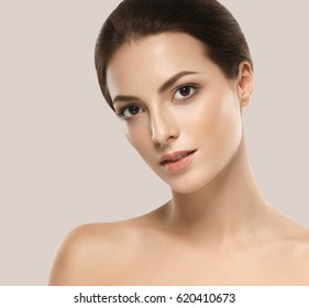 Beautiful woman skincare portrait with hand over beige background. Studio shot.