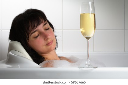 Beautiful woman sleeping in bath with glass of champagne