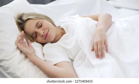 Beautiful woman sleeping in bed, having good dreams, resting in morning, comfort