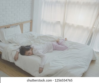 Beautiful woman sleeping in the bedroom. Woman lying face down on the bed.A woman wearing a pajama sleep sleeping on a bed in a white room in the morning.
