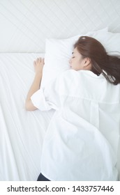 Beautiful woman sleeping in the bedroom.Woman lying face down on the bed.Girl wearing a pajama sleep on a bed in a white room in the morning.Warm tone.