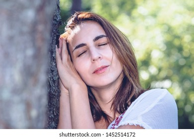 Beautiful woman sleeping in nature with her head leaning on pine tree. Concept of environmental preservation.