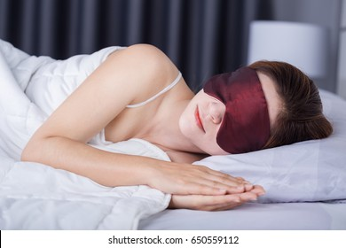 beautiful woman sleeping on bed with eye mask