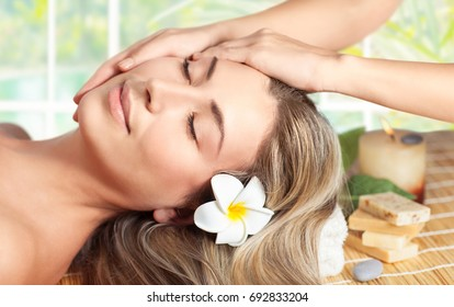 Beautiful woman sleeping on the massage table, attractive model with closed eyes of pleasure enjoying facial massage, peaceful relaxation at spa salon