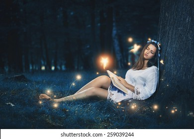 Beautiful woman sleeping peacefully among the forest fairies . Magic and fantasy