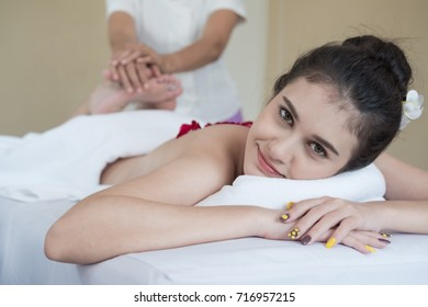 beautiful woman sleeps in bed for a Thai massage. Thai massage by bending legs.