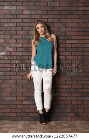 Beautiful Woman In Sleeveless Top And White Distressed Jeans Standing Next To A Brick Wall