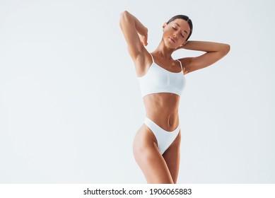 Schöne Frau mit schlankem Körper in Unterwäsche ist im Studio.