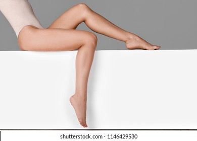 beautiful woman with slim legs sitting on white bench.