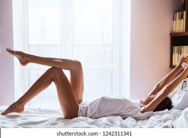 Beautiful woman with slim and long legs lying on the bed. Girl in white t-shirt and shorts, lying on the bed with white bedsheets at the morning. Spending great time at home