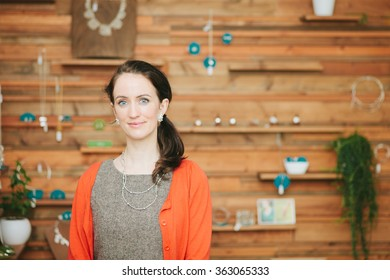 Beautiful woman, small business shop owner looking at camera in her shop