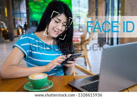 Beautiful woman with smartphone using face ID recognition system in cafe