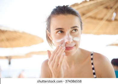 beautiful woman smears face sunscreen at the beach for protection.