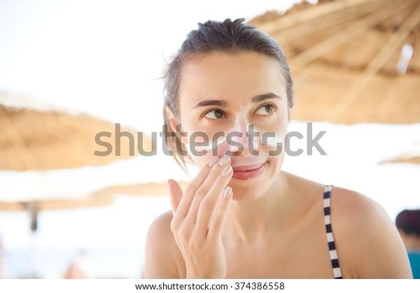 красивая женщина мазок лицо солнцезащитный крем на пляже для защиты.