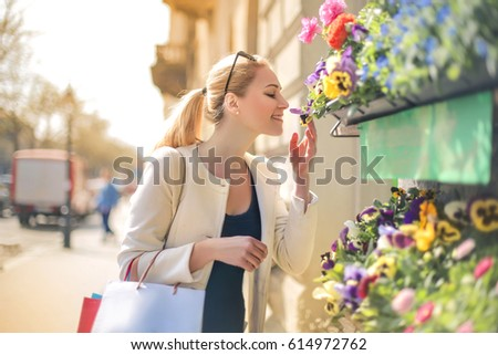 Beautiful woman smelling flowers on the street