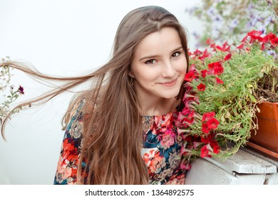 Beautiful woman smelling flowers outdoors, on the street hair flying to the side on a windy summer day, she is looking at camera smiling happy. Mixed race model, asian caucasian girl. Horizontal shot.