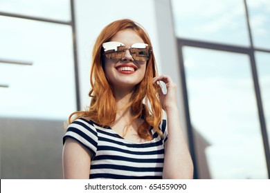 Beautiful woman with a smile, woman with glasses on the background of a building