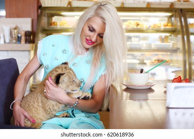 Beautiful woman smiles and holds calf of lion at table in cafe