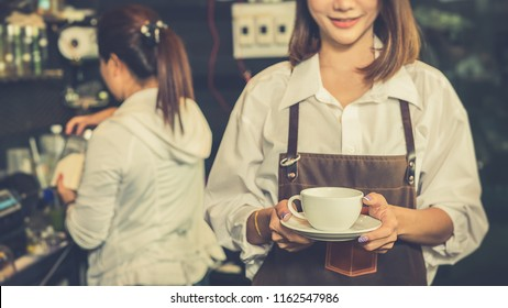 Beautiful woman smiling at camera offers disposable take away hot coffee.