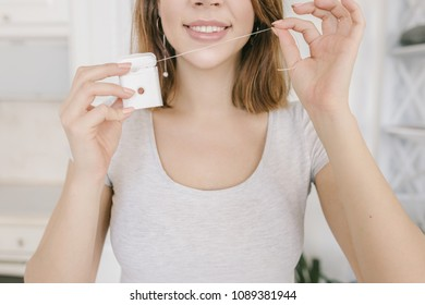 Beautiful woman is smiling with dental floss. Dental health care clinic.