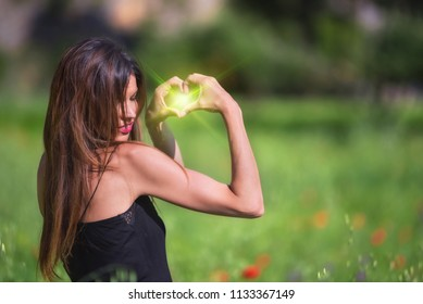 Beautiful Woman smiling. Heart symbol shaped with green flare inside. Love, nature concept. Ecology and sustainability.