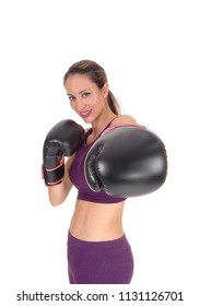 A beautiful woman smiling with her arms up and black boxing cloves