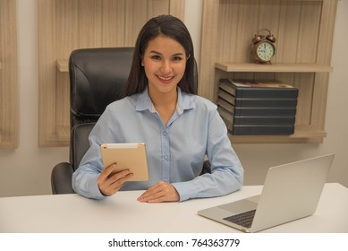 Beautiful woman smiling and holding tablet in the office with laptop computer on her desk