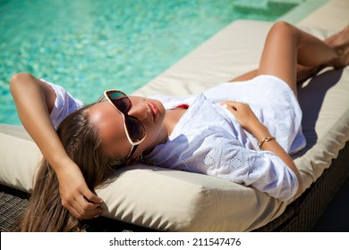 Beautiful woman smiling lying on sun chaise lounge near luxury pool side. Young woman enjoying summer vacation.